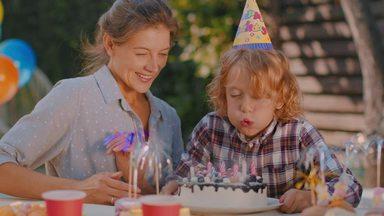 ケーキのろうそくを吹き消す男の子とお母さん