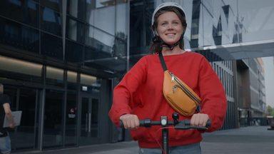 街なかで電動キックボードに乗る女性
