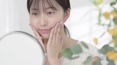 鏡を見て頬を触る女性