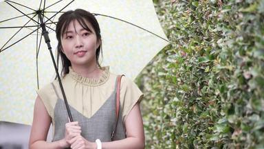 傘をさして外を歩く女性
