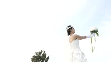 bride with a bouquet toss behind