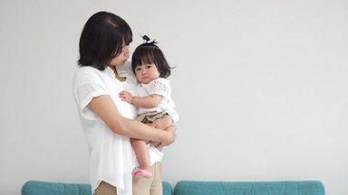 娘を抱っこしながら話し掛ける母親