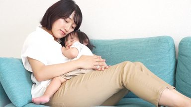 娘を寝かしつけながら眠そうな母親