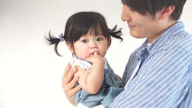 指しゃぶりをする娘を抱っこする父親