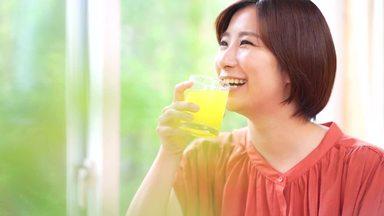 笑顔でオレンジジュースを飲む若い女性