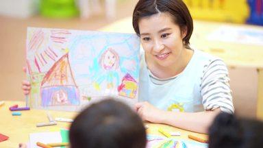 female nursery teacher talking to a child