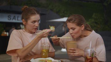 友達の話を聞きながら食事する女性