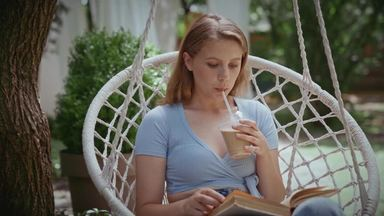 a woman sitting in a hanging chair and reading while drinking cafe au lait