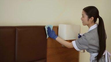 ベッドの埃を拭くホテルのハウスキーパー女性