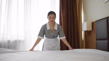 hotel housekeeper spreading sheets
