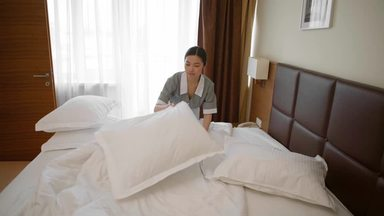 客室のベッドを整えるハウスキーパー女性