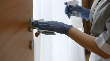 ドアノブを拭くホテルのハウスキーパー女性の手元