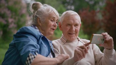 スマホで写真を見て思い出を回顧する祖父母