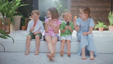 children sitting and eating ice cream happily