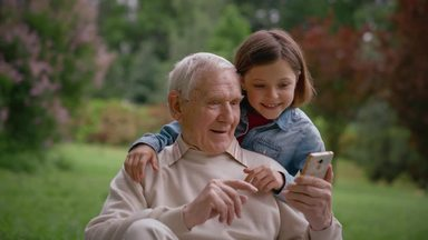 grandpa looking at a girl and a smartphone