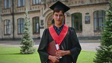 卒業証書を持ちカメラ目線の男性