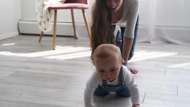 ハイハイする赤ちゃんを捕まえる母親