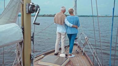 ヨットのデッキでシャンパンを飲む高齢夫婦