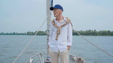 an elderly man standing on a yacht deck and looking out at the sea