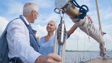 ヨットの上で話をする高齢夫婦